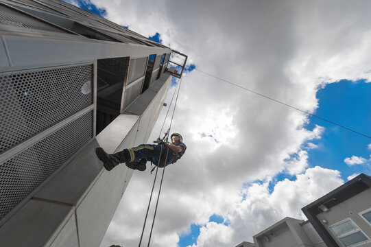 From below of strong firefighter in protective equipment during training with ropes near building on background of blue sky