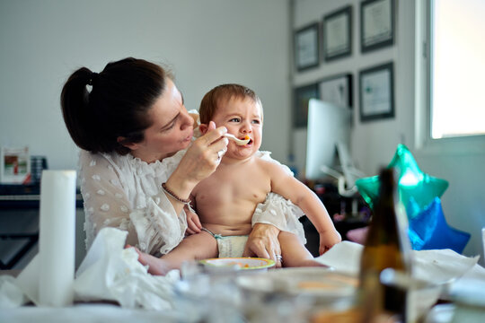 Crying little baby sitting on knees of mother and refusing food from spoon during feeding time at home