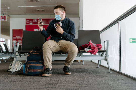 Focused male traveler in casual wear and face mask using smartphone to take selfie holding passport and boarding pass while sitting on chairs with backpack in airport waiting area during coronavirus epidemic