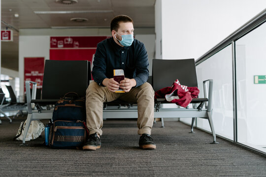 Hungarian male traveler wearing mask with national passport and boarding pass in airport waiting for flight