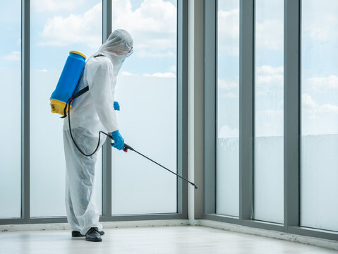 Professional worker man cleaning home office corner by sterilize spray from chemicals sanitizer in backpack with quality service while wearing safety uniform and face mask protect bacteria and virus