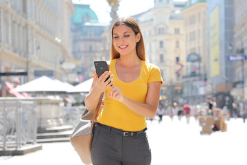 Beautiful smiling woman walking in Graben Street in Vienna typing on smart phone
