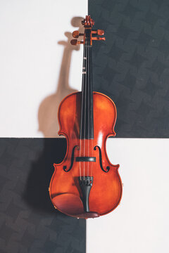 From above of shiny violin with strings placed on chess board pattern floor