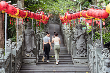 Full body cheerful female friends in tight casual outfits strolling together along stone stairway decorated with red Chinese lanterns in green summer garden