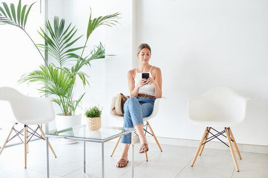 Full body female client sitting on chair and browsing on smartphone while waiting for appointment in lobby of modern clinic