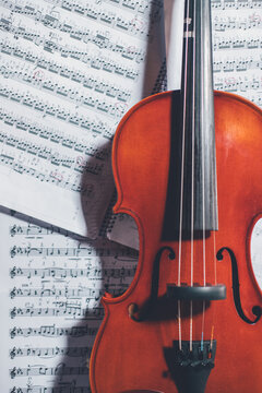 Top view of shiny violin arranged with white music sheets on table at home