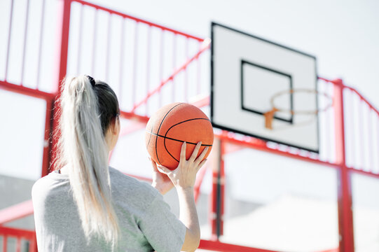 Back view of young sporty woman performing shot while playing basketball alone on sports ground