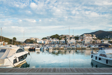 Photo sur Plexiglas Ville sur l eau Wooden pier near vessels and picturesque view of small Llanca municipality with buildings and cloudy sky reflected in calm water in sunny day in Spain