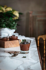 Still-life shoot of chocolate and mint mousse served inside glasses, placed on marble table against decorated background