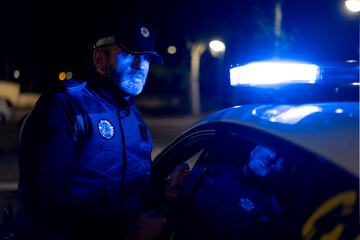 Serious male police officer in uniform standing near automobile with flashing light and speaking on radio set on street at night Fotomurales