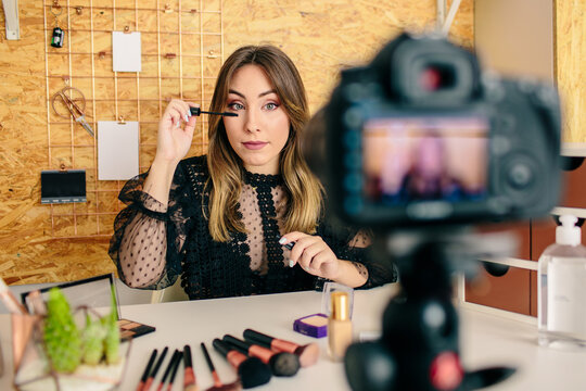 Charming female influencer sitting at table and applying mascara while recording video on professional camera