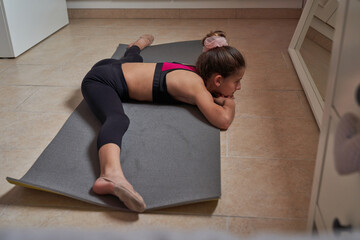 From above slim teenage girl sitting on mat doing splits with arms raised practicing gymnastics in front of mirror