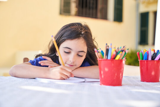 Positive school aged girl while sitting at table and drawing with colorful pencils in copybook during free time