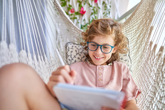 Top view of concentrated boy in eyewear and casual clothes sitting in hammock with pencil and journal while doing homework in apartment