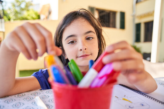 Positive school aged girl while sitting at table and choose drawing with colorful pencils in copybook during free time