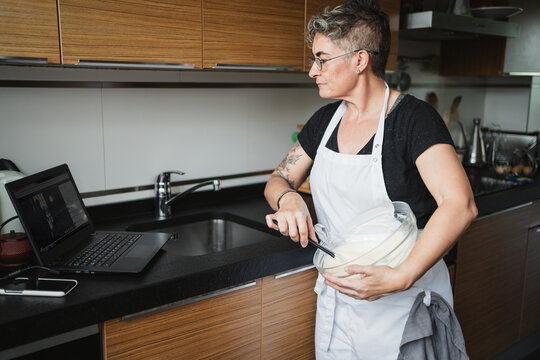Side view of concentrated housewife in apron mixing ingredients in bowl and preparing pastry while watching movie on laptop
