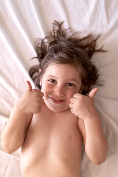 Top view of cheerful kid resting on creased bed sheet doing ok sign with both hands and looking at camera in sunlight