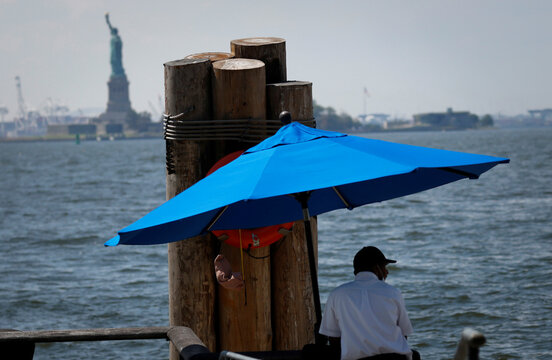 A dock worker stands beneath an umbrella in Battery Park in Manhattan during hot weather in New York
