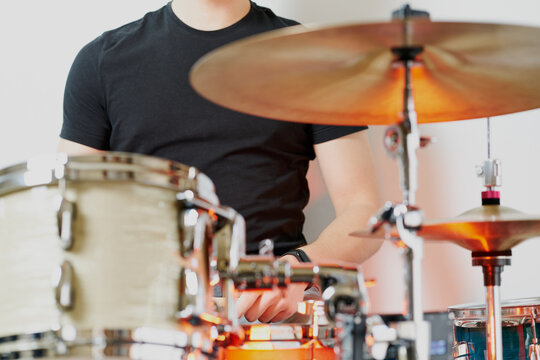 From below cropped unrecognizable casual male drummer playing on drum kit sitting on white background stage