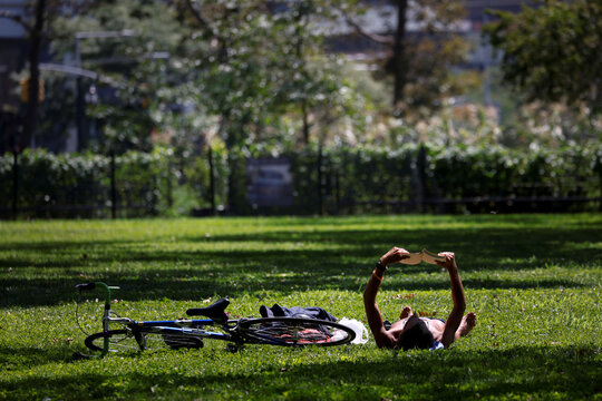 A man reads a book as he lies in the midday sun in Battery Park in Manhattan during hot weather in New York
