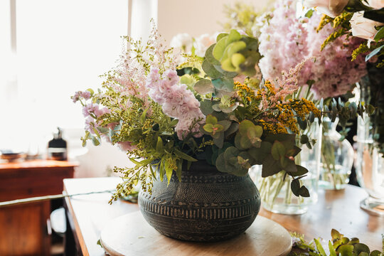 Beautiful bouquet with various flowers including craspedia flowers with green eucalyptus branches arranged in ornamental ceramic pot placed on table in creative floristry studio