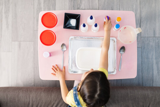 From above of child sitting on comfortable couch while taking plastic bottle with colorant on table with tray and container near spoons