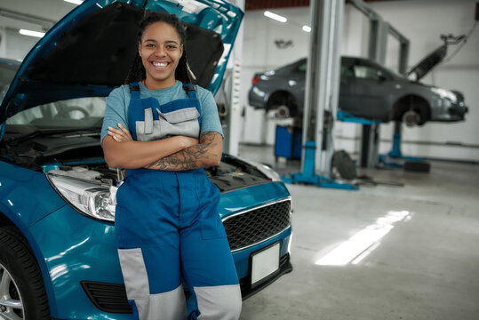 Keep your auto moving. Young african american woman, professional female mechanic smiling at camera, leaning on a car in auto repair shop