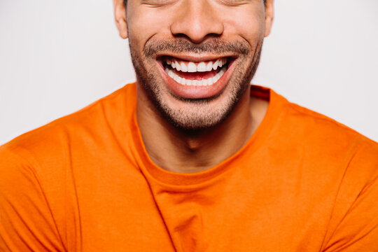Cheerful man cropped on white background. He is wearing an orange t-shirt and looking at camera