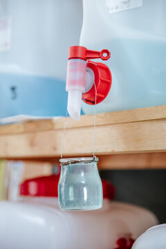 Closeup container with household cleaning chemical product placed on wooden shelf in modern zero waste eco friendly store