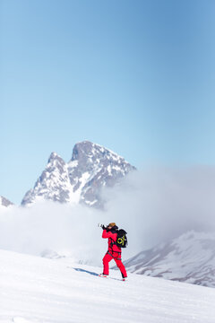 Side view of unrecognizable in red warm outfit and ski boots and with backpack taking photos with professional equipment on mountain slope in sunlight