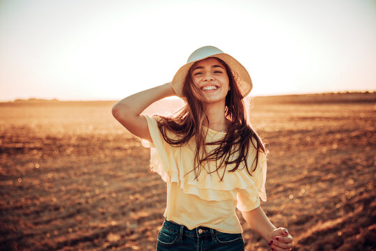Cheerful young woman standing on field during sunset