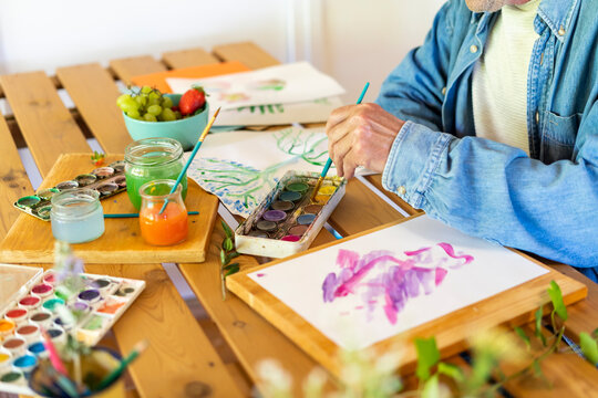 Senior man dipping paintbrush in watercolor paints on table at home