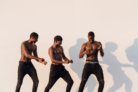 Happy shirtless male friends dancing against white wall
