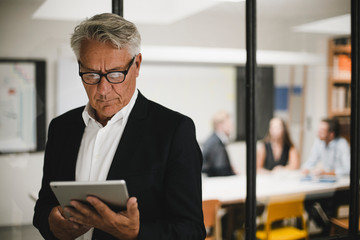 Senior businessman using digital tablet, coworkers working in background