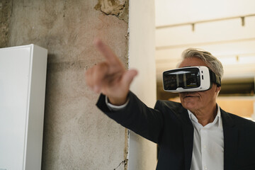 Mature businessman wearing VR glasses, pointing at distance
