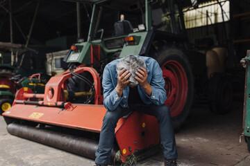 Despaired senior man on a farm sitting on tractor in barn