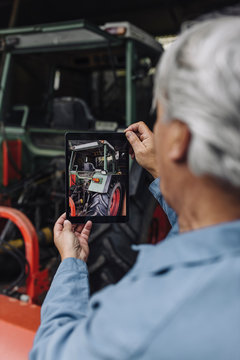 Senior man taking picture of a tractor in barn with a tablet
