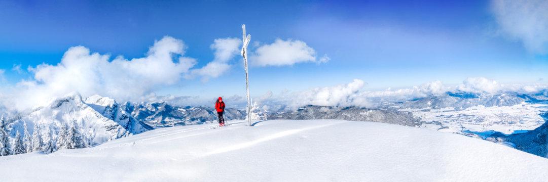 Senior man during ski tour at summit cross, Inzell, Kienberg, Germany