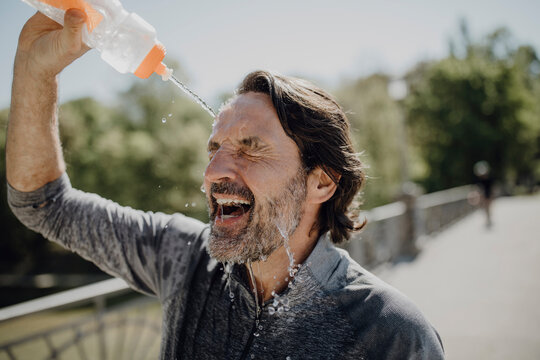Close-up of mature man pouring water on face in park during sunny day