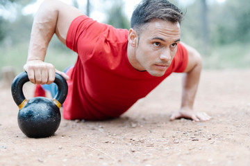 Young athletic man with dumbbell in the woods