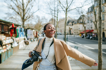 Cheerful woman holding DSLR camera on sidewalk in Paris, France