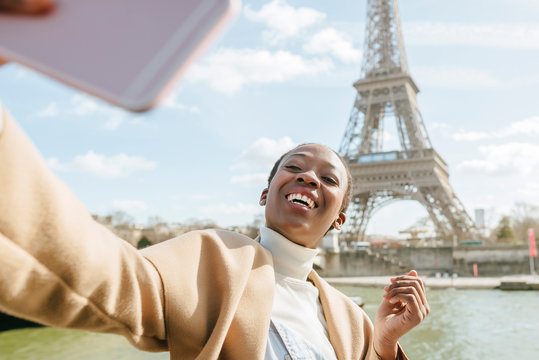 Happy woman taking selfie with Eiffel Tower in background, Paris, France