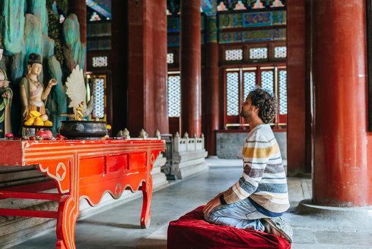 Mid adult man praying in Buddhist temple at Beihai Park, Beijing, China
