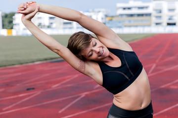 Athletic woman stretching on tartan track