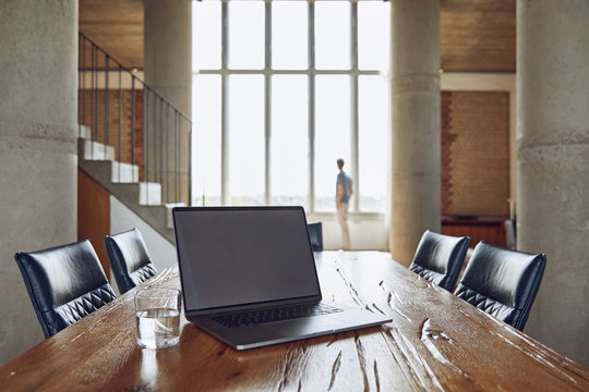 Laptop on wooden table in a loft flat with man at the window in background
