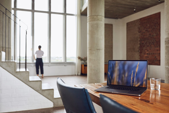 Laptop on wooden table in a loft flat with woman at the window in background