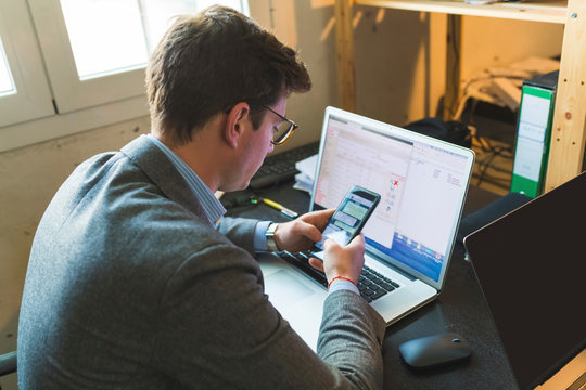 Businessman using smartphone and laptop at desk in office