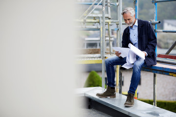 Architect looking at building plan on scaffolding on a construction site
