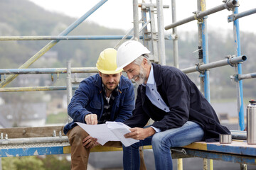 Architect and worker discussing building plan on scaffolding on a construction site