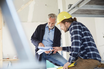 Architect and worker discussing building plan on a construction site